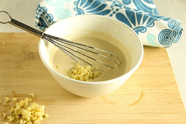 lime-tahini dressing in white bowl on board with fresh ginger