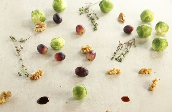 Brussels sprouts, thyme, walnuts, grapes and Balsamic vinegar on white board.