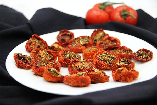 oven-dried tomatoes on white plate on black cloth and fresh tomatoes in background