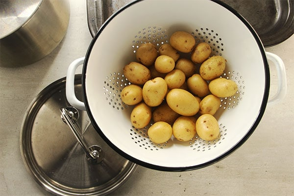 potatoes in white colander with pans in background
