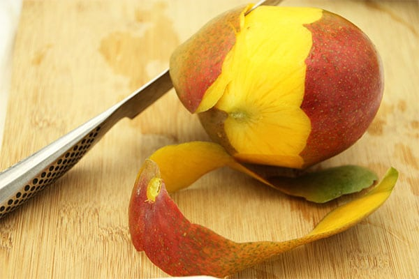 Peeling mangos on board with knife for quick mango curry