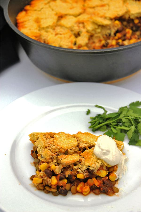 vegan tamale pie on white plate with coriander and vegan sour cream on top.