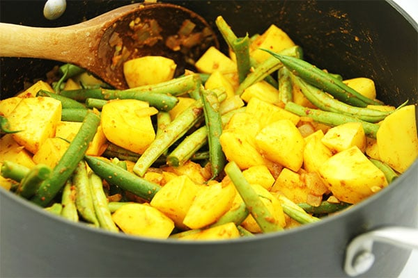 Easy Ethiopian stew in black soup pot highlighting potatoes and green beans