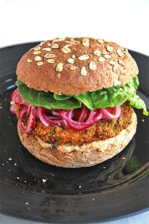 Mediterranean veggie burger recipe makes the perfect burger on a black plate with bun, lettuce and pickled red onions.