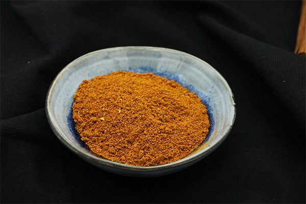 Berbere spice blend in blue dish on black cloth
