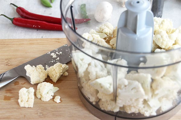 Cauliflower florets in food processor and on wooden board with knife and 2 red chilies in background