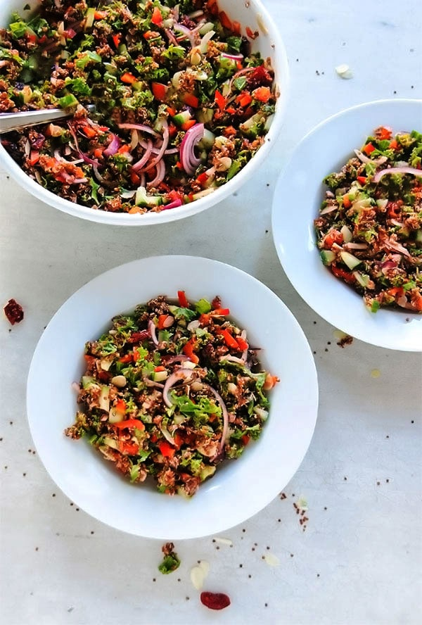 Cranberry quinoa salad in 3 white bowls on white board with almonds, cranberries, and quinoa