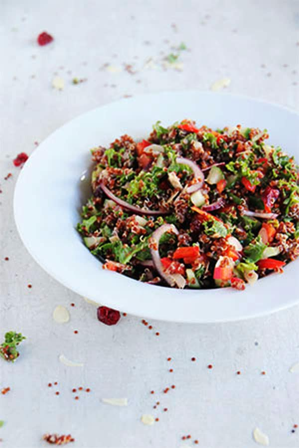 cranberry quinoa salad in white bowl on white board with dried cranberries, almonds and quinoa