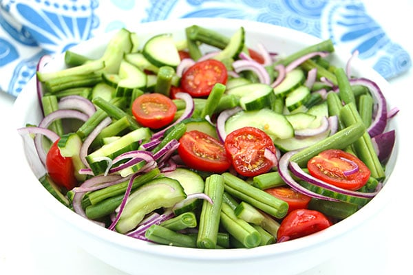 Fresh green bean salad with green beans, tomatoes, cucumber and red onions in large white bowl.