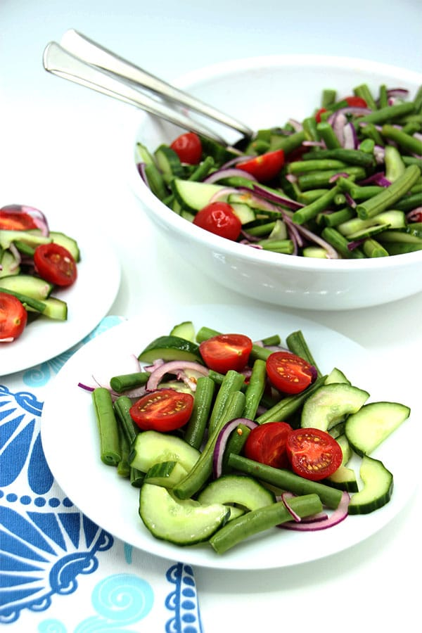 Fresh green beans, tomatoes, cucumber and red onions on 2 white plates with large bowl of salad and blue cloth.