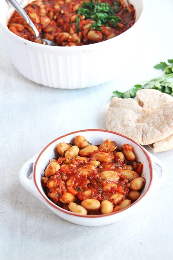 Greek baked beans in white dish with pita bread and casserole dish in background.