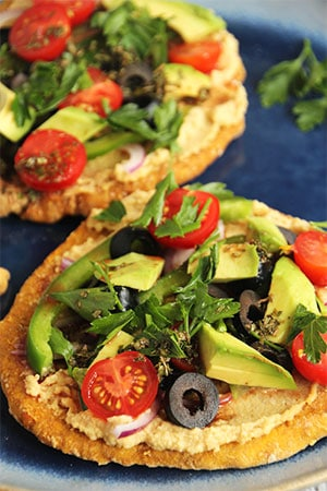2 Greek flatbread pizzas with sweet potato flatbread, hummus, peppers, olives, avocado, onions, tomatoes and parsley on a blue plate.
