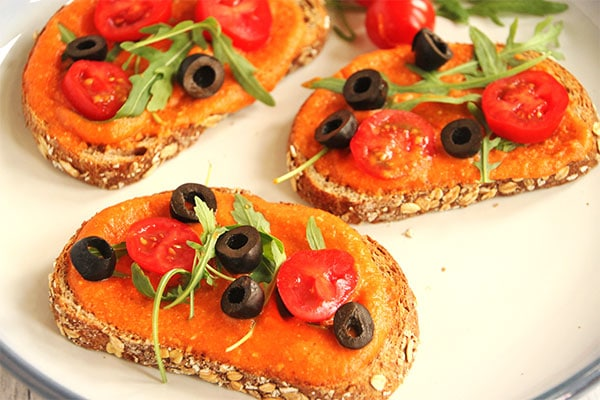 Red pepper Romesco sauce on bruschetta with black olives, tomatoes and arugula on white and blue plate.