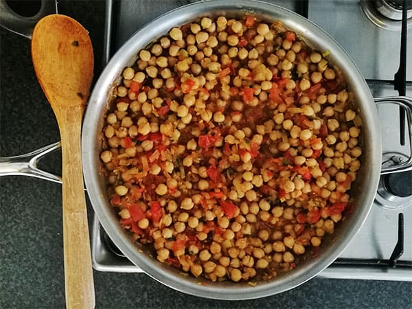 chana masala with tomatoes and chickpeas in stainless steel pan on stove top with wooden spoon.