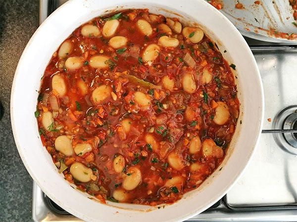 Assembled Greek baked beans in tomato sauce in casserole dish sitting the stove.