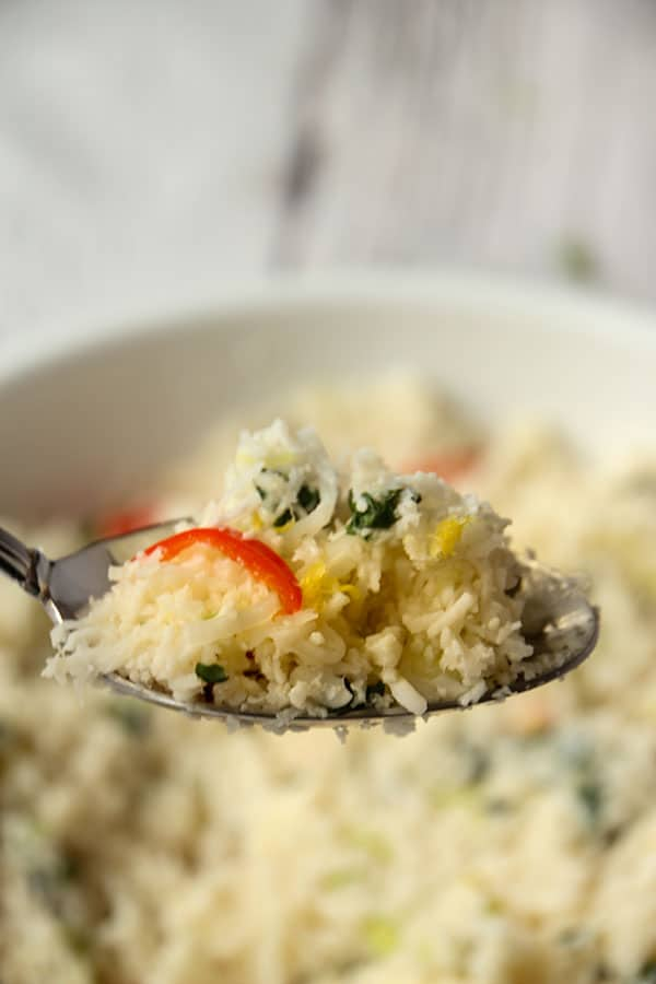 Lemon cauliflower rice is lifted with a spoon over a white bowl.