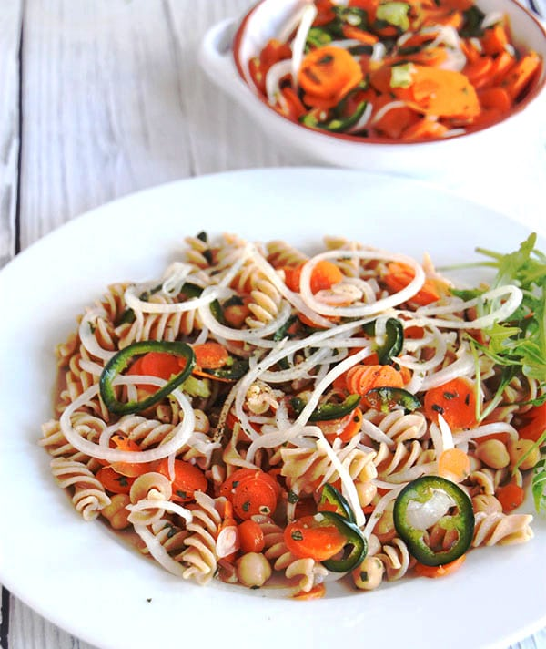 pasta salad with pickled carrots, jalapenos and onions in white bowl.