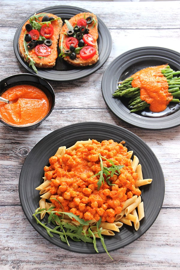 Red pepper Romesco sauce over chickpeas, over asparagus, and bruschetta with sauce in black bowl.