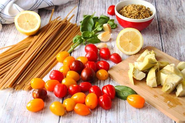 Cherry tomatoes, artichoke hearts, fresh basil, cut lemon, garlic cloves and dry tagliatella pasta on white boards.