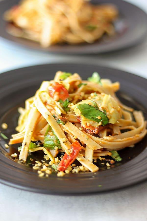 Fresh tomato & artichoke pasta with fresh basil and hemp seed Parmesan on a black plate.