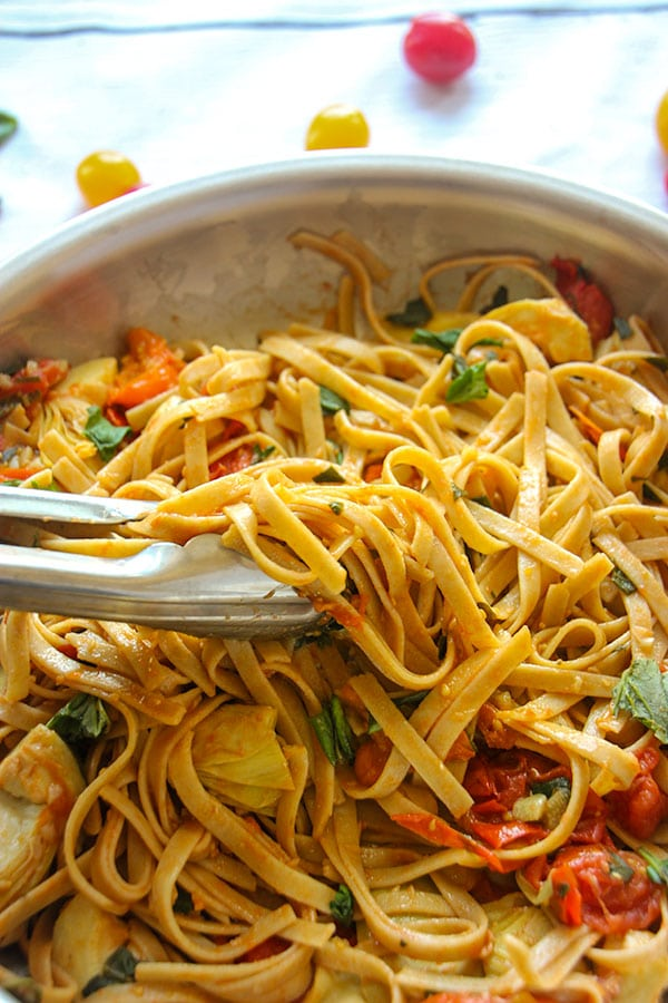 pasta with cherry tomatoes, sliced artichokes and fresh basil is mix with silver tongs in pan.