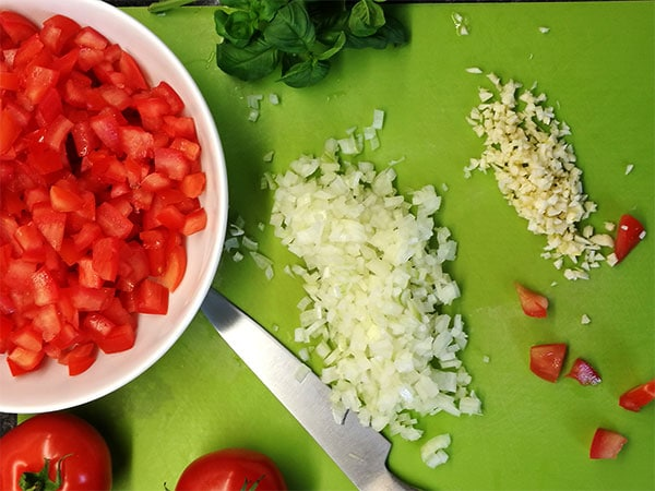 diced tomatoes in white bowl, whole fresh tomatoes, diced onions and minced garlic in green chopping mat.