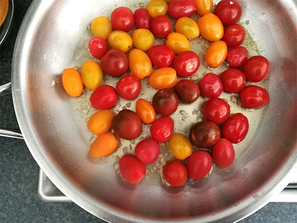Fresh, whole cherry tomatoes are added to broth and garlic in a stainless steel pan on the stove.