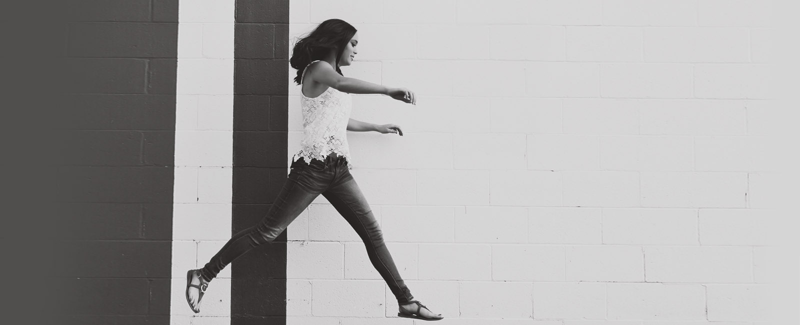 senior girl jumping over curb