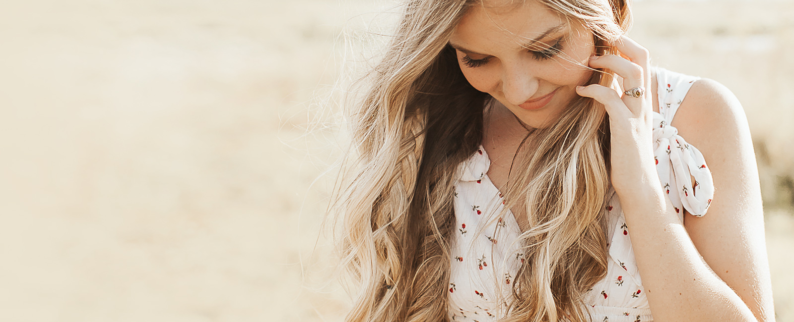 blonde hair girl in field looking down and smiling