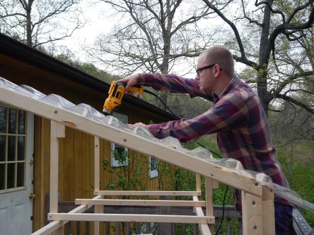 Daniel drilling in plastic sheeting for roof, Jasper, Tennessee