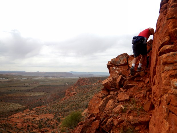 Tom climbing up to the rim, Red Cliffs National Conservation Area, Utah