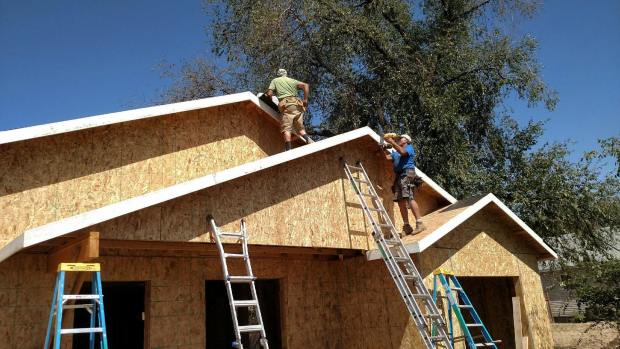 Paul, Tom, and I papering the roof while Bill finishes the fascia on the front gables