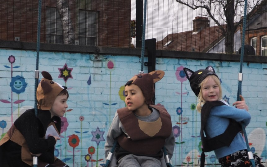 Two boys in a dog and bear costume and a girl in a cat costume are sitting on swings during imaginative play.