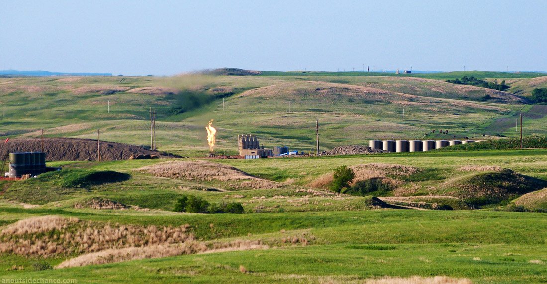 Fracking well pad and gas flare in Bakken district, North Dakota, with gas flare.
