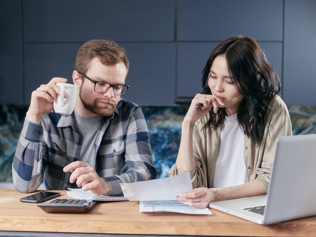 Due persone analizzano un documento per capire quanto costa di contributi un dipendente