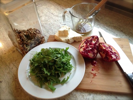 The ingredients for the salad: Arugula, pomegranate seeds, feta, walnuts and the pomegranate vinaigrette