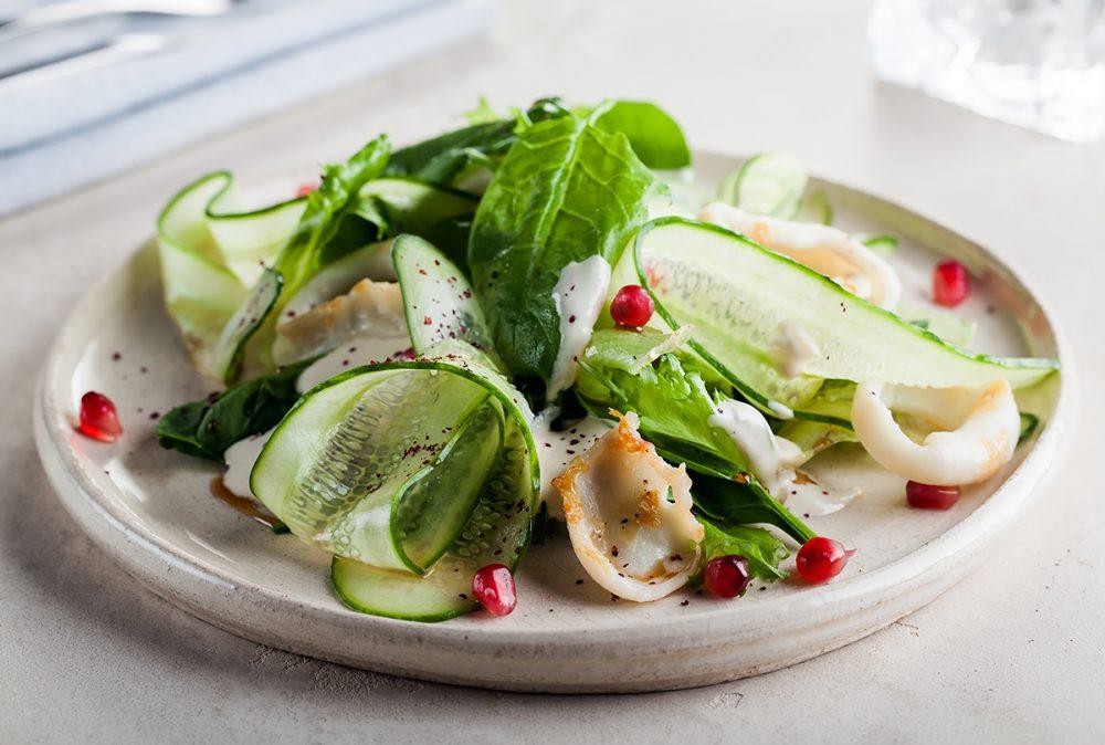 теплый салат из обжаренного кальмара с листьями салата, зернами граната, сумахом и тхиной