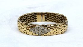 An 18ct yellow gold and diamond set bracelet of snake skin effect, set with thirty brilliant cut diamonds, marked 750, approximately 51.2 grams. Sold for £1,200 at Anthemion Auctions