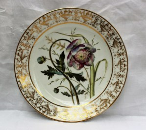 A Swansea porcelain plate, from the Gosford Castle service, the border decorated with gilt vases and anthemions, the centre painted with a floral specimen and leaves, unmarked, 22.8cm diameter. Sold for £1,300 at Anthemion Auctions