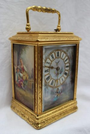 A 19th century gilt brass and repeating carriage clock, the case with leaves and scrolls, set with three porcelain panels decorated with figures in a landscape, with Roman numerals, striking on a gong, 17cm high in a carrying case. Sold for £1,250 at Anthemion Auctions