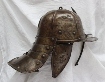 A 17th century German Zischagge, lobster tail helmet with a one piece hemispherical skull, with a pair of pendent cheek pieces, stamped XVII to the underside of the peak. Sold for £780 at Anthemion Auctions