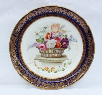 A 19th century porcelain plate painted to the centre with a basket of flowers on a plinth produced for the Lysaght service, the border in royal blue with gilt highlight; these plates were produced by Swansea and Coalport, 24cm diameter. Sold for £750 at Anthemion Auctions