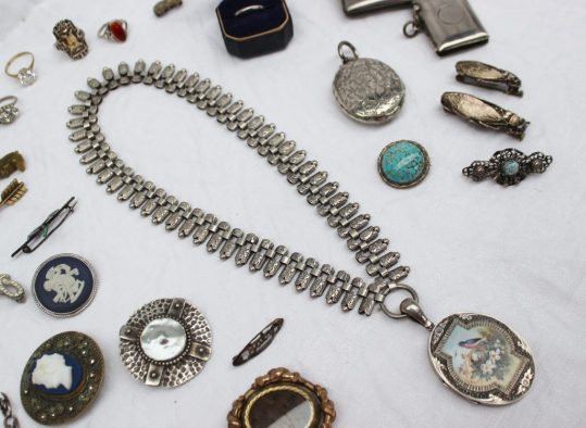 A white metal wedding band marked Plat, approximately 2.8 grams, together with a silver locket with enamel decoration of a bird on its nest, a white metal chain, silver vesta cases, and assorted costume jewellery including rings, fly brooches, other brooches etc. Sold for £750 at Anthemion Auctions