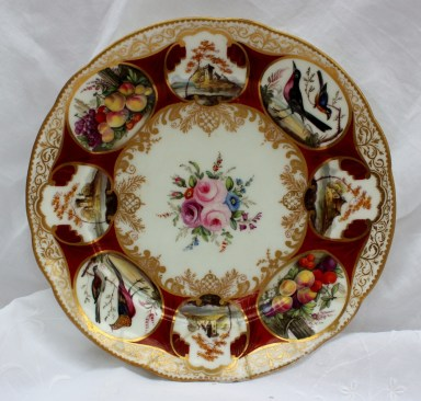 A Nantgarw porcelain plate painted with vignettes of birds, castles and fruit to a red ground, the centre painted with roses, from The Duke of Cambridge service, impressed NANT-GARW C.W., 23.5CM high. Sold for £720 at Anthemion Auctions