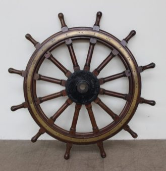 """A large brass and hardwood ships wheel, with twelve spokes, the cast plate to the centre inscribed """"Stephens - Adamson Mfg co of Canada Ltd Belleville Ontario"""". Sold at Anthemion Auctions for £780"""
