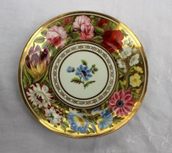 A Swansea 'Marquis of Anglesey' pattern porcelain plate with a thick gilt rim, painted with a gilt border and roses and other garden flowers, the centre painted with a single flower, unmarked, 20.5cm diameter. Sold for £680 at Anthemion Auctions