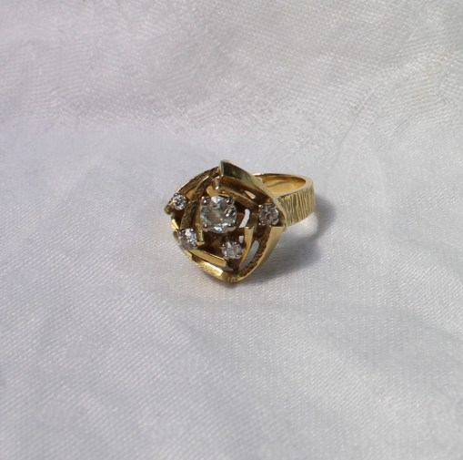 An 18ct yellow gold dress ring set with five old cut diamonds in a geometric pattern on a textured shank, approximately 11 grams, hallmarked for London, 1976, AMC makers mark. Sold for £750 at Anthemion Auctions