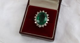 An emerald and diamond ring the central oval faceted emerald measuring 17mm x 13mm surrounded by eight brilliant cut and eight trillion cut diamonds to an 18ct white gold claw setting and shank, size O. Sold for £1,350 at Anthemion Auctions