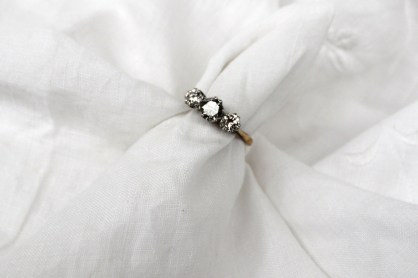 A three stone diamond ring, the central round brilliant cut diamond approximately 0.5 of a carat the two diamonds either side each approximately 0.25 of a carat to a white metal claw setting and yellow metal shank marked 18ct & Plat. Sold for £820 at Anthemion Auctions