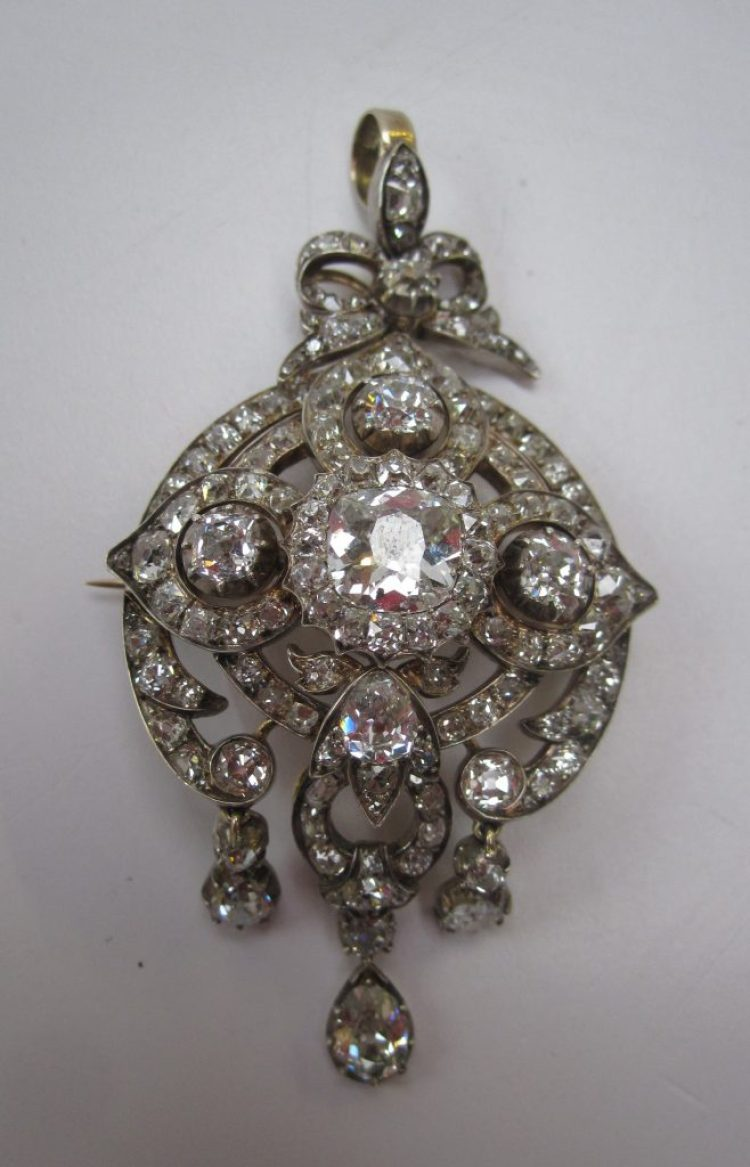 A Victorian diamond brooch/pendant, the centre circular cushion cut diamond is set within a surround of sixteen smaller cushion shaped diamonds, the bow loop above concentric diamond set circles with pendant drops, to a white and yellow metal setting, in a fitted box for Bracher & Sydenham, Reading
